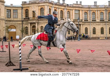 Gatchina St. Petersburg Russia - September 30 2017: Horse show of Cossacks on the parade ground of the Gatchina Palace. The Cossack rides with a sword.