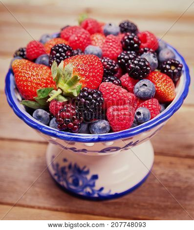 Mixed ripe sweet berries in a blue and white bowl on a wooden background with selective focus. Blueberries raspberries strawberries and blackberries. A delicious desert for example for Christmas. With space for text.