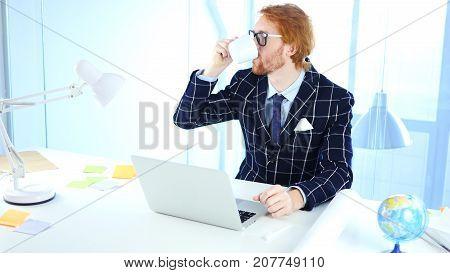 Redhead Businessman Drinking Coffee At Work, Relaxing Freelancer Designer