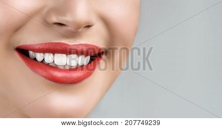 Beautiful smile young woman  with whitening teeth. Dental photo. Perfect fashion lips makeup. Health happy female smile. Macro close-up shot of woman's mouth. Care about tooth