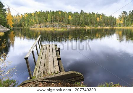 Old wooden bridge in a lake in autumn colorful forest in background