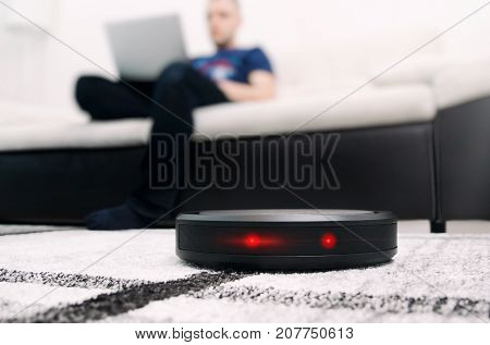 Robotic vacuum cleaner working on carpet. Abstract science fiction red eyes sensor concept