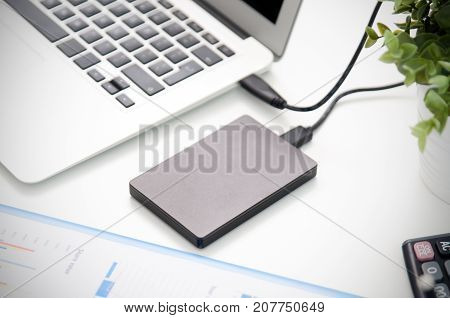 External backup disk hard drive connected to laptop. hard drive backup disk external computer data usb concept poster