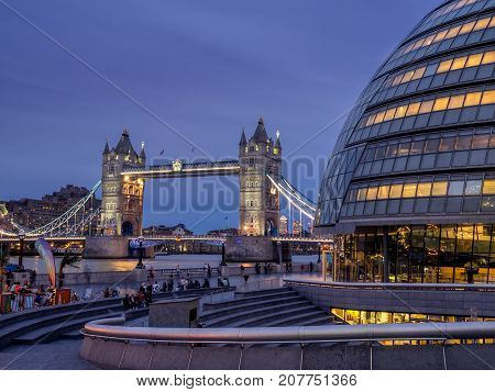 LONDON UK - AUG 1: London City Hall and Tower Bridge on August 1, 2017 in London UK. The City Hall has an unusual bulbous shape was designed by Norman Foster and opened in July 2002.