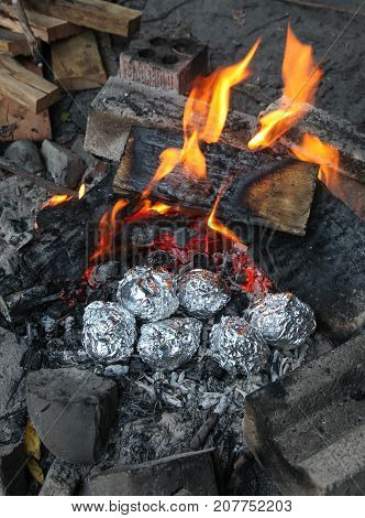 A camp fire with potatoes roasting in aluminium foil in the hot coals. Campfire cooking is one of the great things about camping.