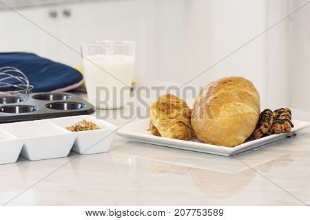 Freshly baked baguette and bread with ingredients for whole grain healthy breadGranola and milk and eggs in the kitchen.