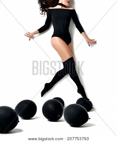 Young beautiful brunette woman walking jumping levitating above black balloons on the floor