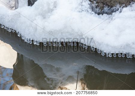 Small round icicles over water perfect reflection