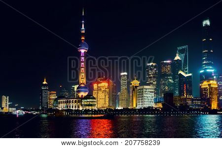 Shanghai, China - Nov 4, 2016: Night view of the Shanghai City skyline. Features the Oriental Pearl TV tower and Huangpu River. Some low-lying haze around, imparting an atmosphere to the scene.
