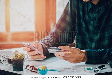 Hipster man hands holding smart phone and using credit card for online shopping.Online shopping concept.Close up