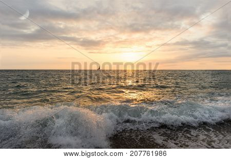 Sunset sailboat is a sailboat sailing along the ocean at sunset with the moon rising in the sky as a wave rolls to to the sea shore.