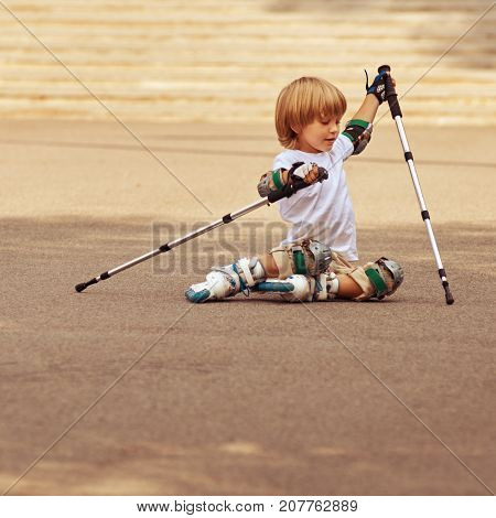Little boy trying to rise after rollerskating fall, image with toning