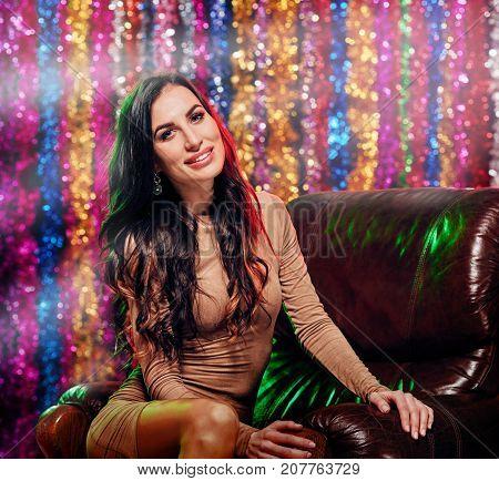 Beautiful elegant woman sitting in luxurious armchair in night club