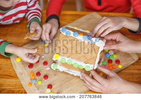 family decorates gingerbread house. children's hands and gingerbread house close-up on a wooden table
