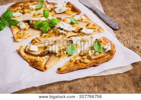 Traditional pizza with pear nuts and blue cheese on a wooden background. Selective focus.