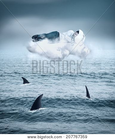 Business man sleeping on a cloud above sharks in the ocean.