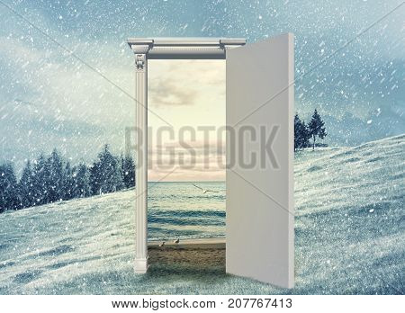 Opened door on a field during winter which leads to the sea during summer. Changing season through the door concept.
