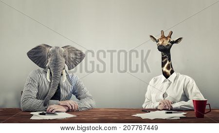 An elephant and a giraffe dressed as business people .