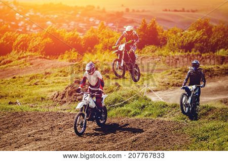 Team Racer on motorcycle participates and jumps. Close-up. concept of extreme motocross, sports racing. ray of light