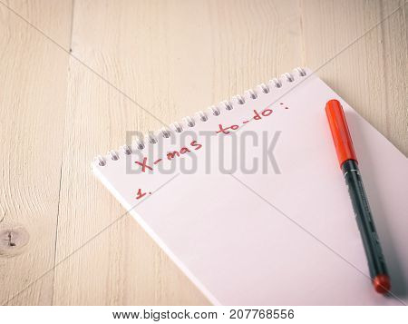 Christmas gifts shopping planning. Make shopping or to-do list for Christmas. Notebook with red pen on white wooden background. Toned image. Copy space.