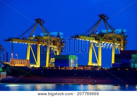 Shipping port. Logistics and transportation of international import export container cargo ship with crane bridge in harbor at twilight dusk for shipping and transportation industry