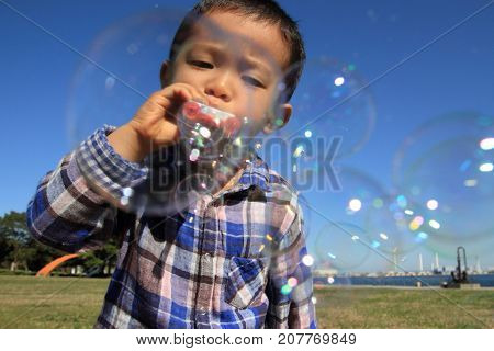 Japanese Boy Playing With Bubble (3 Years Old) On The Grass
