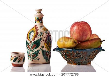 Still life with apples pears ceramic handmade bottle a cup a colander. The bottle and the cup are painted according to the samples of the late nineteenth century in the technique Kosovo ceramics