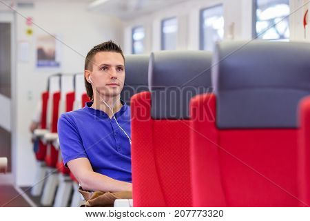 Young man listen music traveling by train
