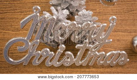 Xmas Ornaments Merry Christmas Text with Baubles and Pinecones on Wooden Table Sign for Christmas Celebration.