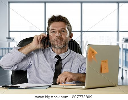 corporate portrait of happy successful businessman in shirt and tie smiling at computer desk with mobile phone confident and trustful in communication concept at modern office