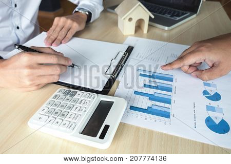 Man sign a home insurance policy on home loans Agent holds loan investment chart graph documents pointing and calculating table installment payment Real Estate concept.