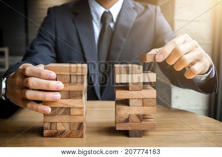 Alternative risk concept plan and strategy in business Young intelligent businessman playing the wood game hands of executive cooperate placing wood block on the tower Collaborative management.