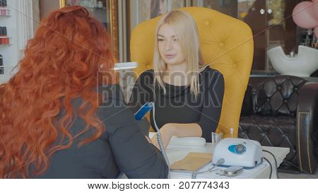 Portrait of blonde woman at manicure procedure. Hardware manicure in a beauty salon. Manicurist is applying electric nail file drill to manicure on female fingers.