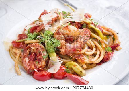 Italian linguine alla gamberetti with vegetable and parmesan as close-op n a plate