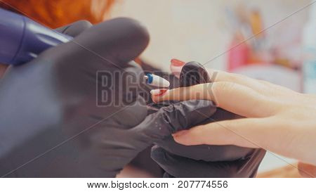 Close-up of manicurist removing the old gel polish using elecrtric nail file, slow motion. The removal gel cutter tool. Beauty, spa and relax concept.