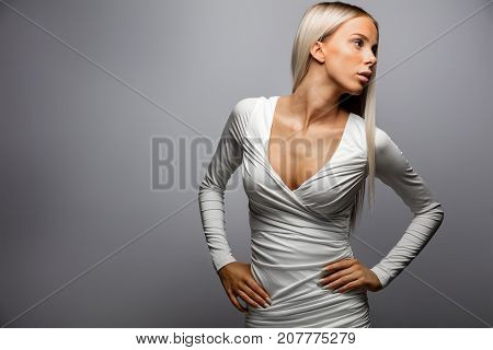 Beautiful young woman with hands on hip looking away over gray background