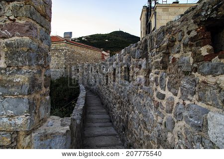 BUDVA, MONTENEGRO - SEPTEMBER 14, 2013: It is a narrow passage through the medieval fortress wall that surrounds the old town.