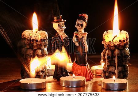 figures of two skeletons of the man and the woman against the background of the burning candles in the form of skeletons, Halloween