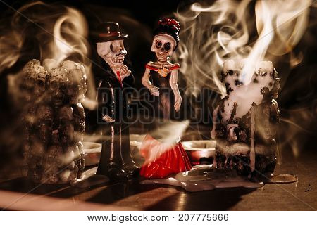smoke from extinct candles has filled space and has shrouded figures of the man and the woman in the uniform of skeletons