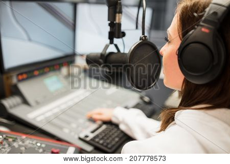 Young female jockey wearing headphones while using microphone in radio station