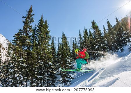Skier Freerider Jumping From A Snow Ramp In The Sun On A Background Of Forest And Mountains