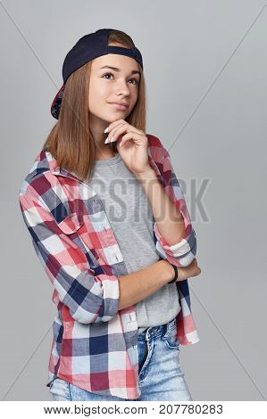 Pensive teen girl wearing checkered shirt and baseball cap looking up in thoughts over grey background, half length portrait