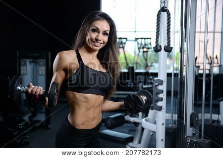 Sexy Athletic Young Girl Training Arms In Gym