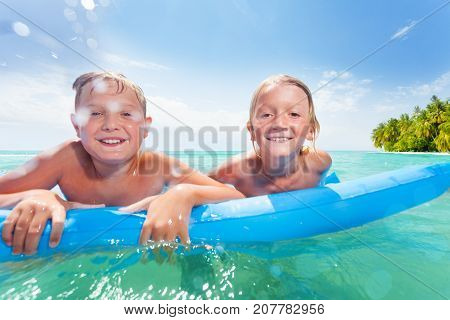 Two happy boys on the blue inflated matrass smiling swimming in the ocean