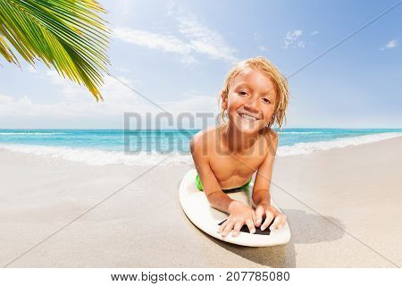 Handsome smiling blond boy laying on surf board resting after surfing on palm sandy beach