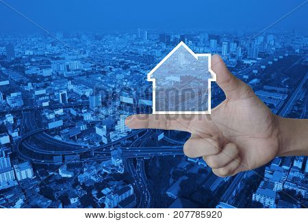 House icon with copy space on finger over modern city tower street and expressway Real estate concept