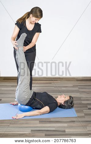 Trainer helps a woman senior in her pilates exercices.