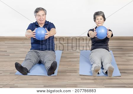 Two Senior People In A Gym Class Lying On Mats Doing Pilates Exercise With Pilates Ball
