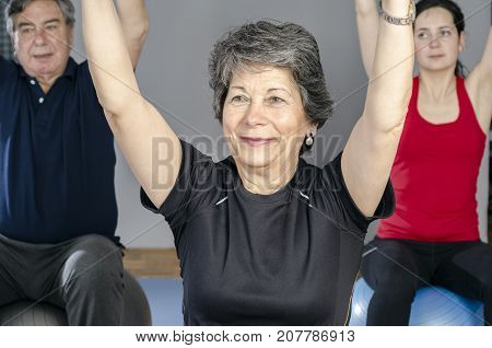 Diverse group of people a gym class sitting on Pilates ball doing ring Pilates exercise.