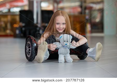 Happy And Smiling Girl With Mini Segway And Plush Bear Doll At Trading Mall. Teenager Riding On Hove